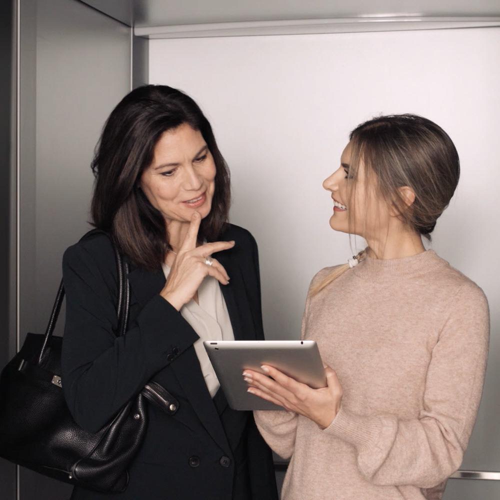 Eine junge Frau erklärt einer Managerin ein Projekt im Aufzug